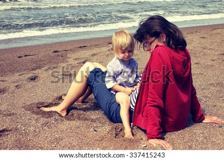 Mother and her little daughter sitting on the beach with serious facial expressions. Retro effect applied   - stock photo