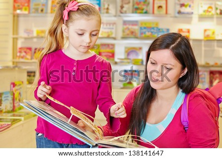 Mother and her little daughter view fold-out book in book department at store - stock photo