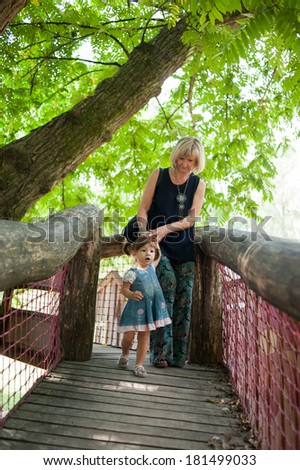 Mother and her little girl are walking in on the wooden bridge. - stock photo