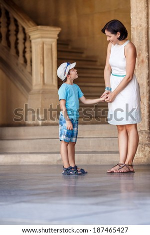 Mother and her little son at courtyard of the Palace of Charles V (Palacio de Carlos V) in La Alhambra, Granada, Spain - stock photo