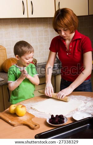 Mother and her little son making pie with apples and blackberry - stock photo