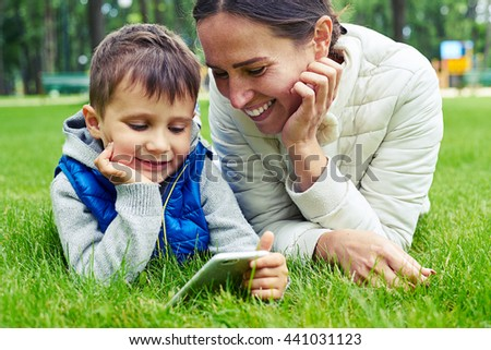 Mother and her little son spend sunny day in park lying on grass and watching something on the phone - stock photo