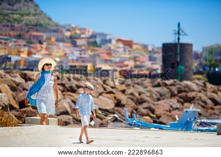 Mother and her little son walking outdoors in town Castelsardo, Sardinia, Italy - stock photo