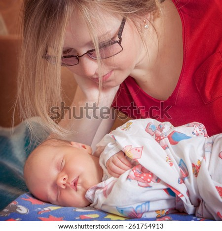 Mother and her Newborn Baby. Happy Mother admires sleeping child.  soft image of Beautiful Family. Maternity concept. Parenthood. Motherhood. - stock photo