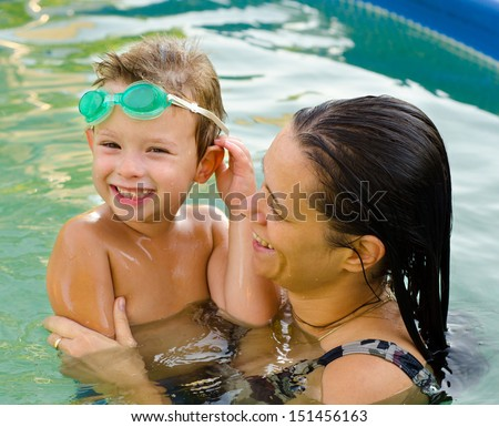 Mother and her son having fun in the swimming pool. - stock photo