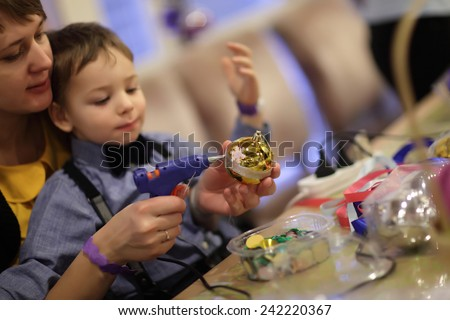 Mother and her son making Christmas decorations in the classroom - stock photo