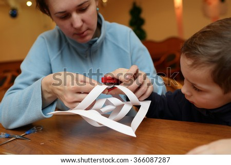 Mother and her son making paper snowflakes at workshop - stock photo