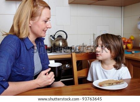 Mother and her son sits at kitchen table and have a conversation - stock photo