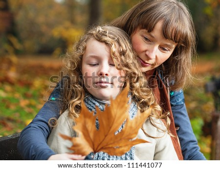 Mother and her teenager daughter sitting on a bench in an autumn park and looking at fallen leaf - stock photo