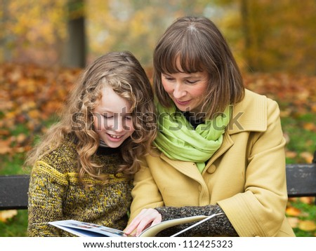 Mother and her teenager daughter sitting with a book on a bench in an autumn park - stock photo