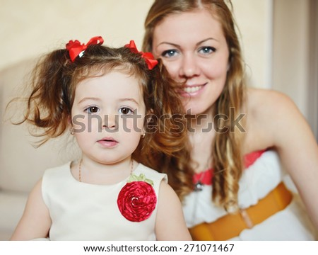 mother and her toddler daughter are wearing dresses - stock photo