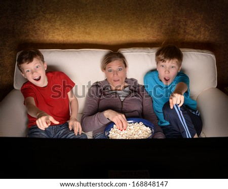 Mother and her two boys watching a Suspense or Thriller Movie at home - stock photo