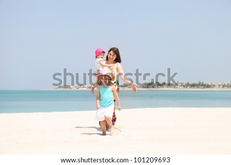 Mother and her two little daughters having fun on the beach - stock photo