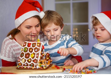 Mother and her two little sons preparing a gingerbread cookie house at christmas time - stock photo