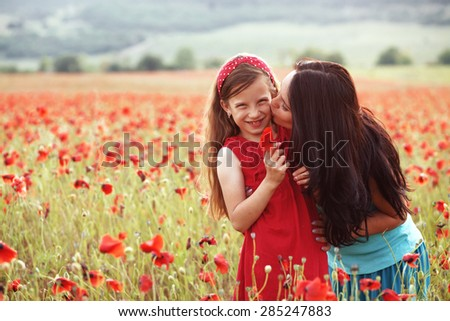 Mother and her 7 years old preteen child playing in spring poppy field in soft sunlight. Mom kissing daughter. - stock photo