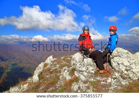 Mother and kid after climbing on sunny mountain top - stock photo