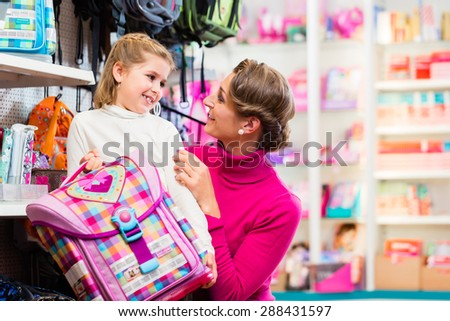 Mother and kid becoming a student buying school satchel or bag in store - stock photo