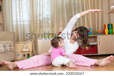 mother and kid doing gymnastic at home - stock photo