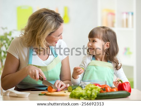 mother and kid girl cooking and cutting vegetables on kitchen - stock photo