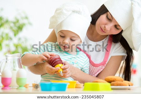 Mother and kid girl making cookies together - stock photo