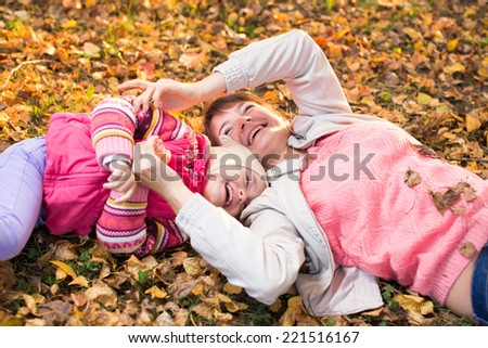 mother and kid have fun laying on autumnal leaves outdoors - stock photo