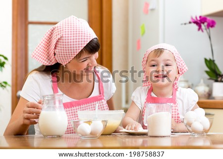 Mother and kid preparing cookies together at kitchen - stock photo