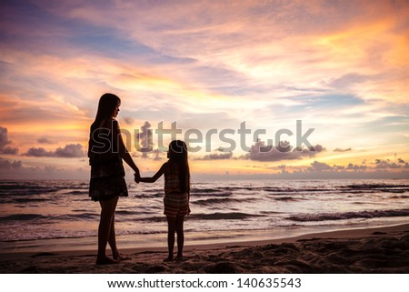 Mother and kid silhouettes on sunset beach - stock photo