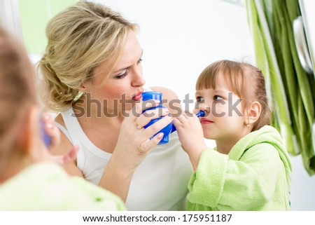 mother and kid with neti pot ready for nasal irrigation or douche - stock photo
