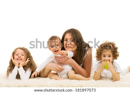 Mother and kids lying down on fur carpet home - stock photo
