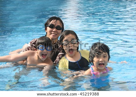 Mother and kids playing happily in the pool - stock photo