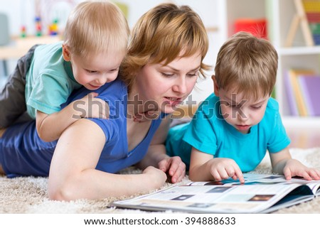 Mother and kids reading book at home - stock photo