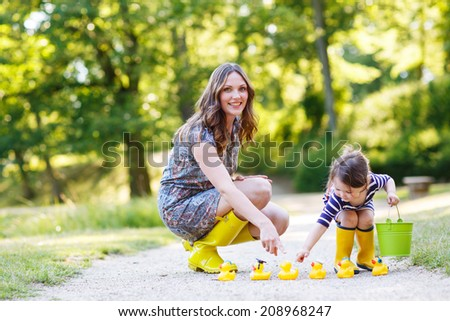 Mother and little adorable daughter in yellow rubber boots, family look, playing with duck toys in summer park - stock photo
