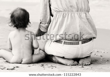 Mother and little baby having fun on the beach - stock photo