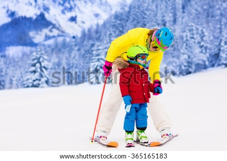 Mother and little child skiing in Alps mountains. Active mom and toddler kid with safety helmet, goggles and poles. Ski lesson for young children. Winter sport for family. Little skier racing in snow - stock photo
