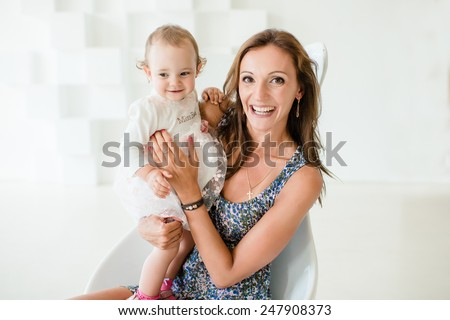 Mother and little daughter are smiling - stock photo
