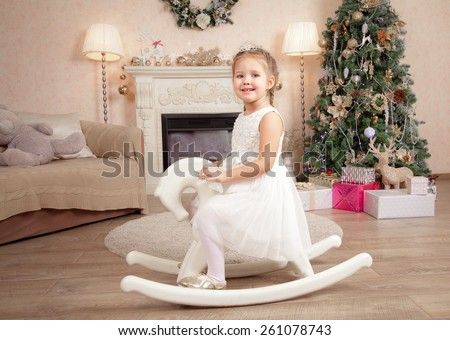 Mother and little daughter decorate a Christmas tree at home - stock photo