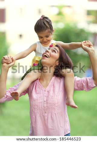 Mother and little daughter having fun outdoors and expressing affection. - stock photo
