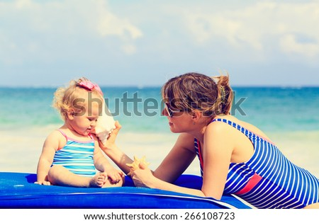 mother and little daughter listening shells on summer beach - stock photo