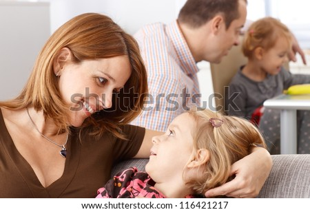 Mother and little daughter looking to each other's eyes smiling happily. - stock photo
