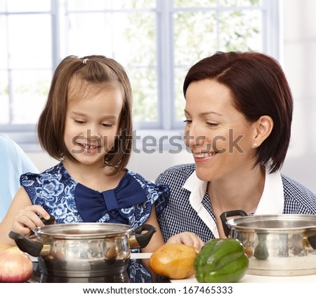 Mother and little daughter playing cooking, both smiling. - stock photo