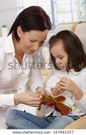 Mother and little daughter playing, sewing a toy bear. - stock photo