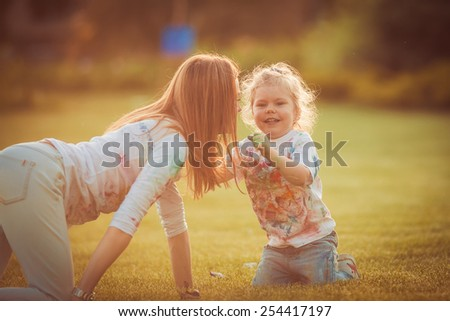 Mother and little daughter playing together in a park - stock photo