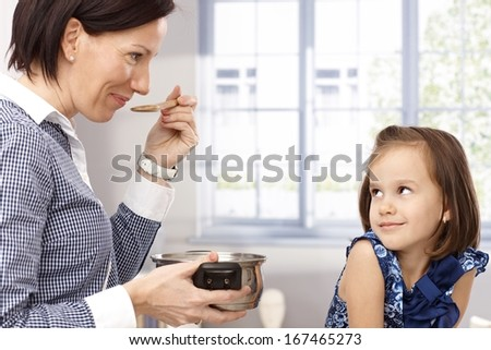 Mother and little daughter tasting their cooking by wooden spoon. - stock photo