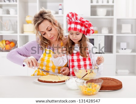Mother and little girl making a cake together - spreading the filling - stock photo