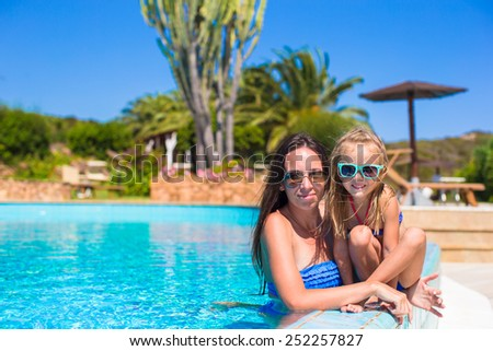 Mother and little girl relaxing in luxury quiet swimming pool - stock photo