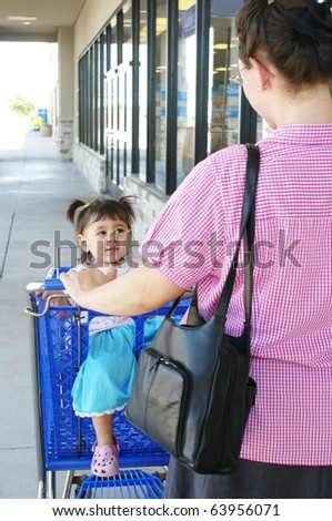 Mother and little girl shopping, outdoors with shopping cart - stock photo