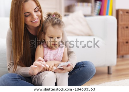 Mother and little girl using mobile phone at home  - stock photo