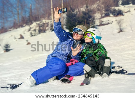 Mother and little son selfie on the ski slope resort - stock photo