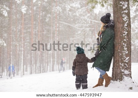 Mother and little toddler boy walking in the winter forest and having fun with snow. Family enjoying winter. Child and woman watching falling snow outdoors. Winter, Christmas and lifestyle concept. - stock photo