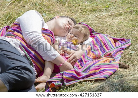 Mother and lovely one year old baby sleeping on colorful blanket in sunlight - stock photo